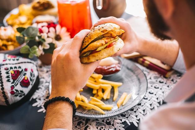 Homme tenant un burger au poulet servi avec des frites et de la sauce