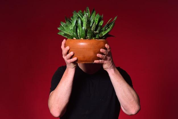 Homme tenant un cactus devant son visage