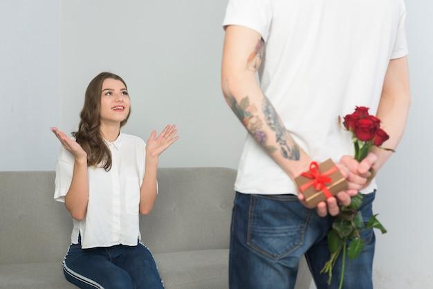 Homme tenant des cadeaux pour jeune femme derrière le dos