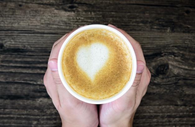 Un homme tenant un café au lait avec du lait de coeur d'art isolé sur une table en bois brun. appartement poser avec une tasse de café saint valentin concept.