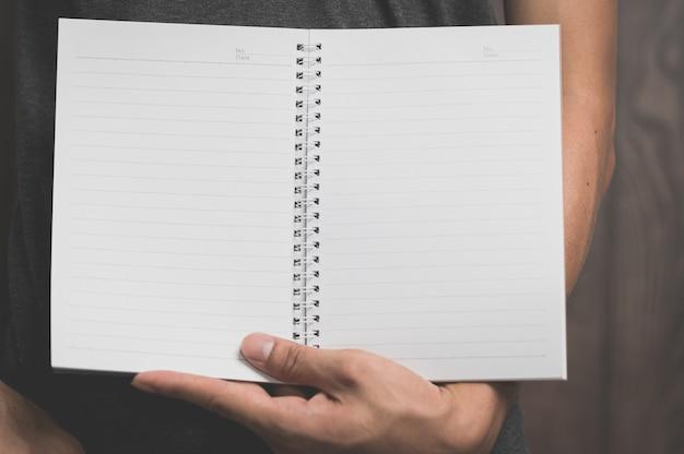 Un homme tenant un cahier en papier