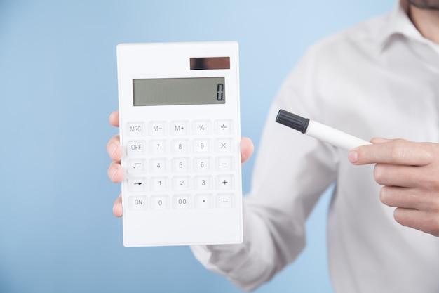 Homme tenant la calculatrice sur fond bleu calcul des investissements