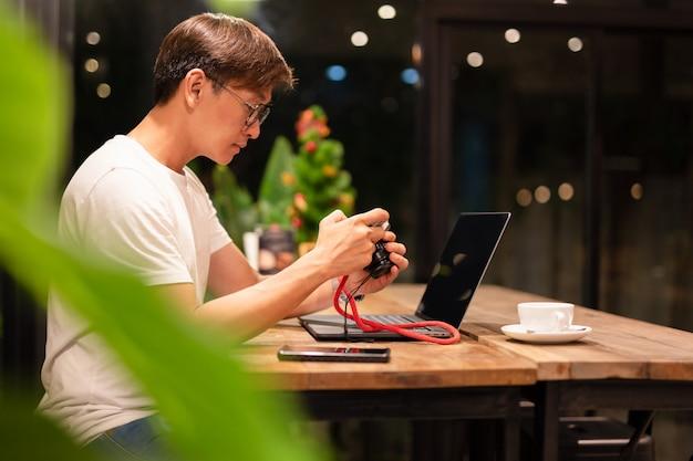 Homme tenant une caméra numérique sans miroir, vérifiant la photo avec l'ordinateur portable sur la table.