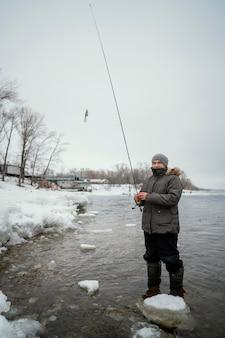Homme tenant une canne à pêche