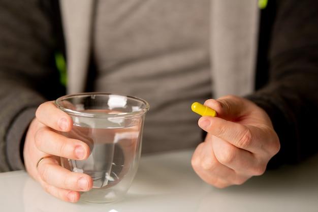 Homme tenant une capsule de vitamine et un verre d'eau. photo en gros plan