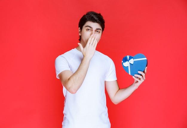 Homme tenant une carte-cadeau en forme de coeur et de la pensée.