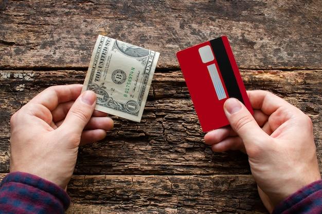 Homme tenant une carte de crédit et de l'argent