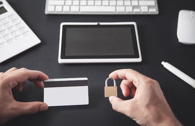 Homme tenant une carte de crédit et un cadenas. sécurité des cartes de crédit