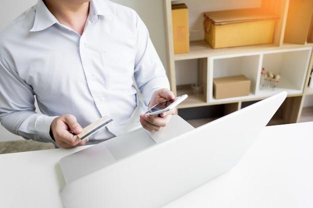 Homme tenant la carte de crédit en main et entrant dans le code de sécurité à l'aide d'un téléphone intelligent sur le clavier de l'ordinateur portable, concept de magasinage en ligne