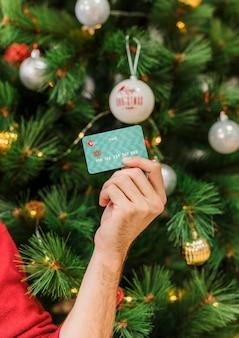 Homme tenant une carte de crédit en main