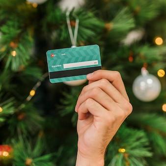 Homme tenant une carte de crédit en plastique à la main