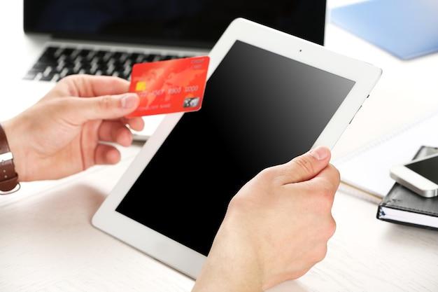 Homme tenant une carte de crédit et une tablette sur le lieu de travail