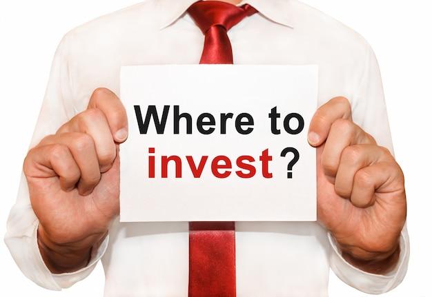 Homme tenant une carte avec un texte où investir.