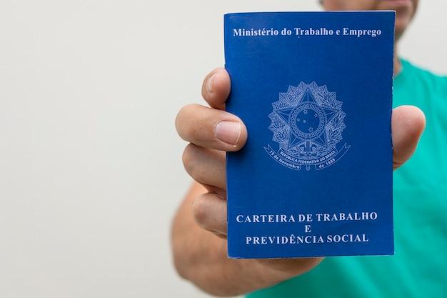 Homme tenant une carte de travail brésilienne