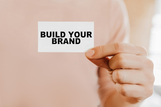 Homme tenant une carte de visite avec construisez votre marque