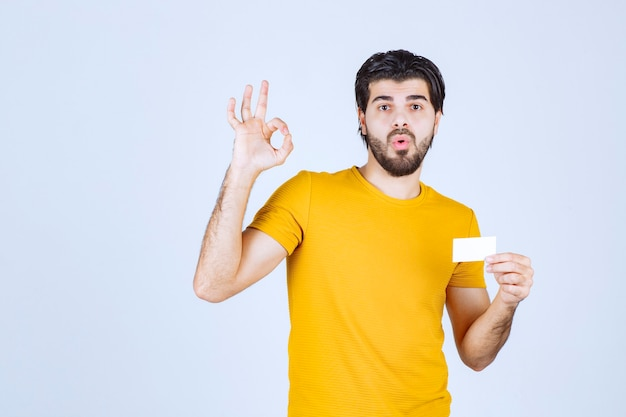 Homme tenant une carte de visite et montrant un geste ok