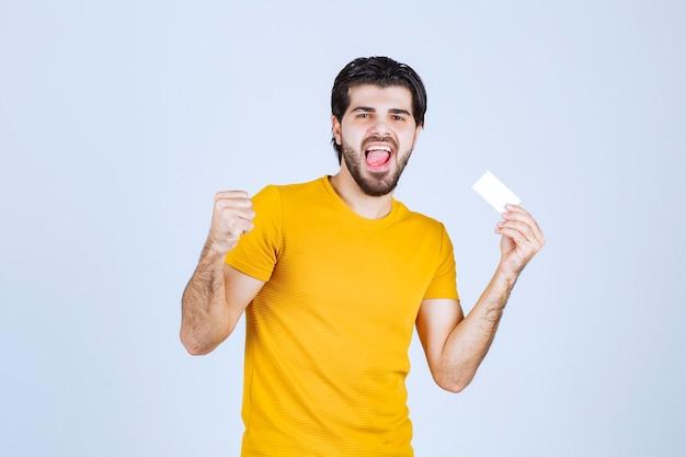 Homme tenant une carte de visite et montrant son poing.