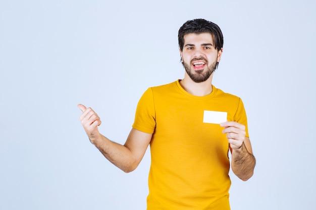 Homme tenant une carte de visite et pointant vers son partenaire.