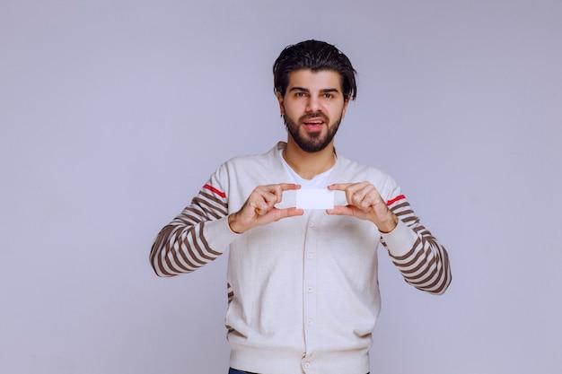Homme tenant une carte de visite et la présentant ou la recevant.