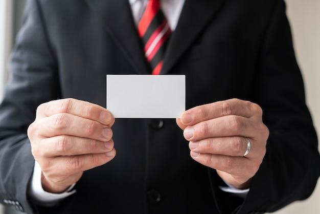 Homme tenant une carte de visite vierge