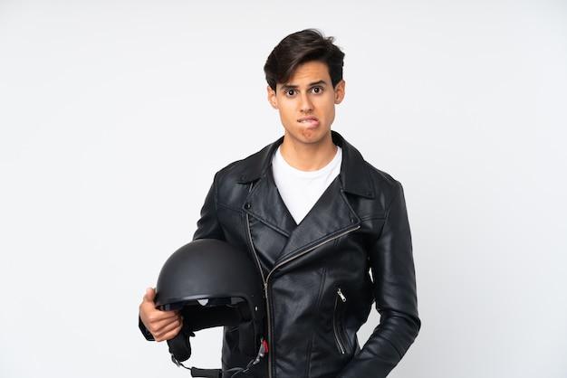 Homme tenant un casque de moto sur un mur blanc ayant des doutes et avec une expression de visage confus
