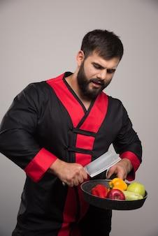 Homme tenant une casserole avec des légumes et un couteau.