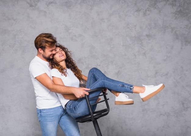 Homme tenant une chaise avec une femme