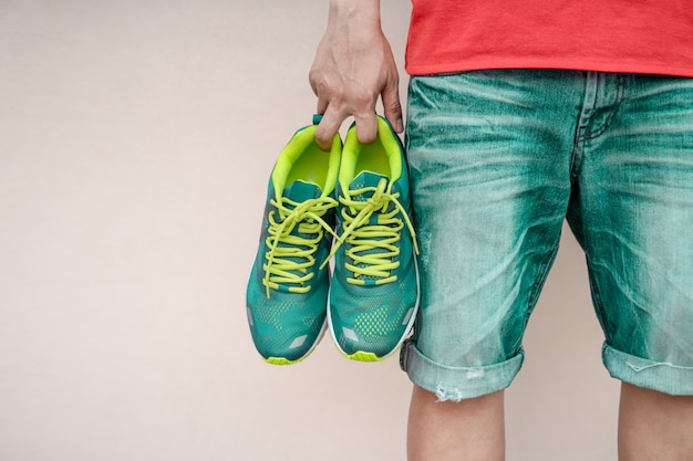 Homme tenant des chaussures de sport à la main.