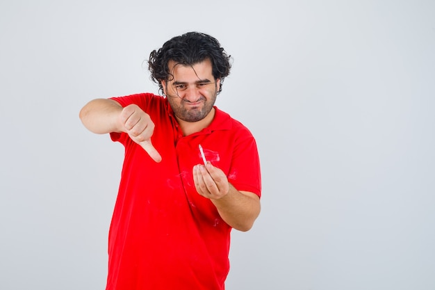 Homme tenant la cigarette, montrant le pouce vers le bas en t-shirt rouge et à la recherche concentrée