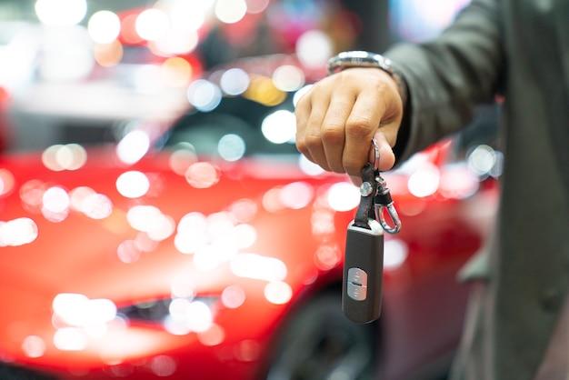 Homme tenant les clefs de voiture avec voiture sur fond