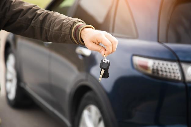 Homme tenant les clés sur la surface d'une voiture bleue