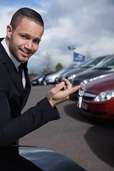Homme tenant des clés de voiture avec un doigt à l'extérieur