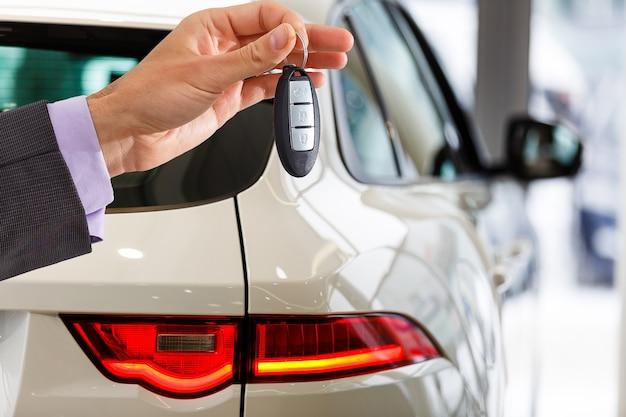 Homme tenant des clés de voiture avec voiture sur fond