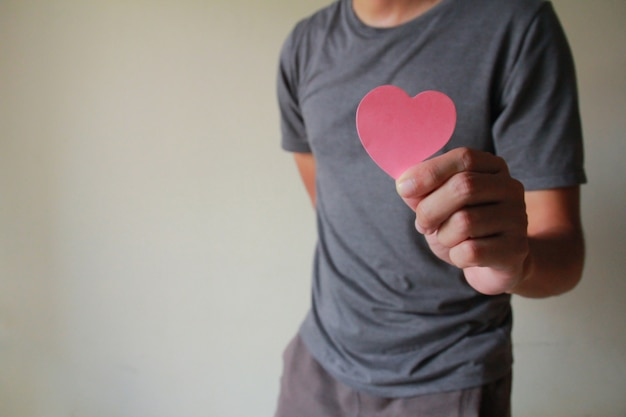 L'homme tenant un coeur en papier.