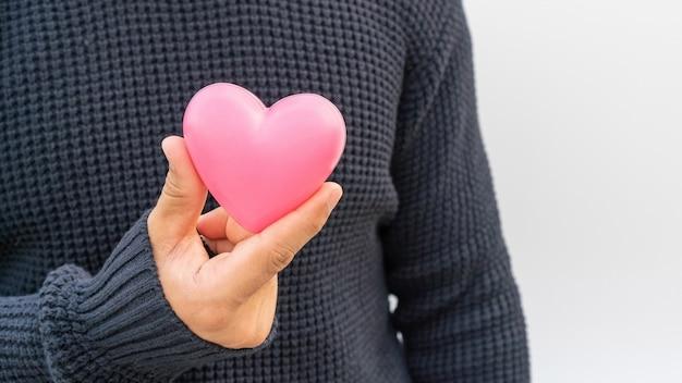 Homme tenant un coeur rose sur blanc