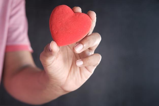 Homme tenant coeur rouge sur fond noir