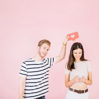 Homme tenant comme icône sur sa petite amie à l'aide de téléphone portable