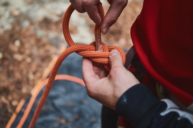 Homme tenant une corde et se préparant à gravir les montagnes. équipement d'escalade en détail photo en gros plan.