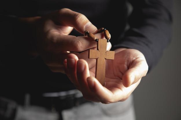 Un homme tenant une croix en bois à la main