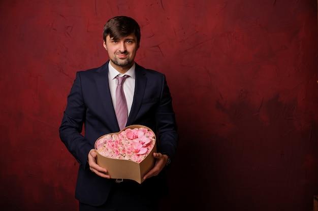 Homme tenant dans une main une boîte de fleurs roses