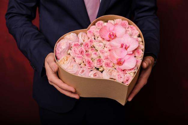 Homme tenant dans une main une boîte rose d'orchidées, de roses et de pivoines