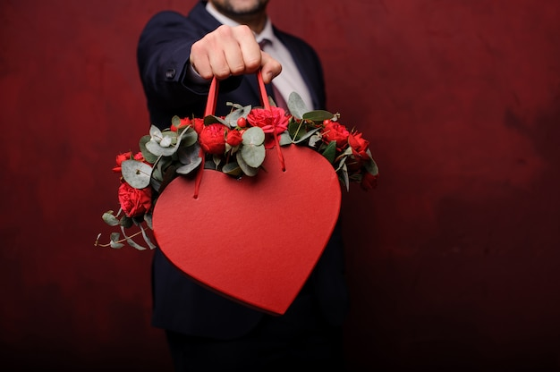 Homme tenant dans une main une boîte rouge de roses