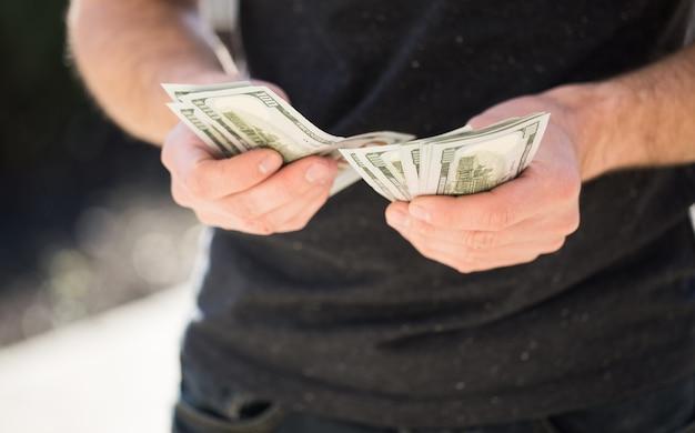 Homme tenant dans les mains dollar