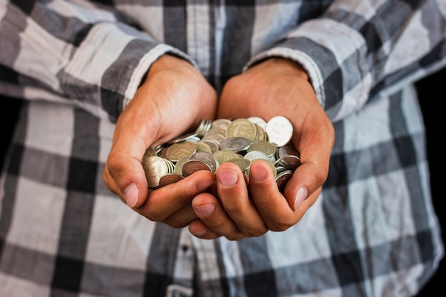 Homme tenant dans les mains économiser des pièces