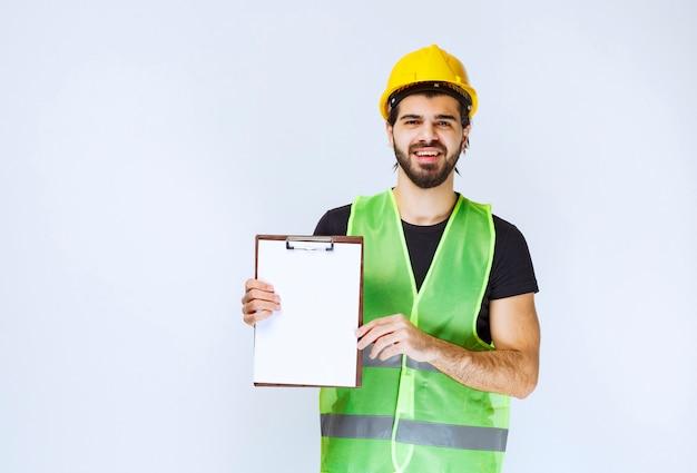 Homme tenant et démontrant la version finale du projet de construction.