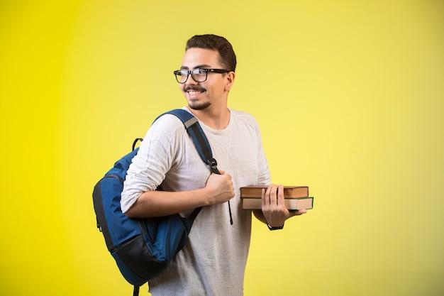 Homme tenant deux livres et souriant.