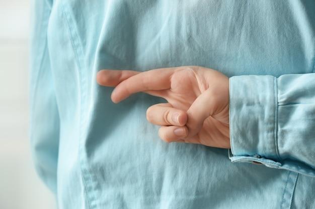 Homme tenant les doigts croisés derrière son dos, gros plan.