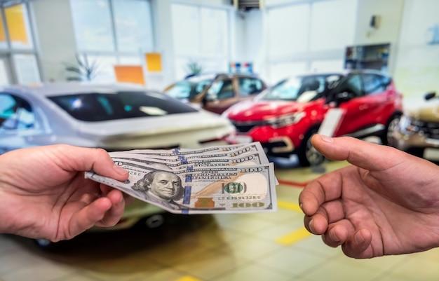 Homme tenant des dollars à louer ou acheter une voiture en arrière-plan. concept d'entreprise