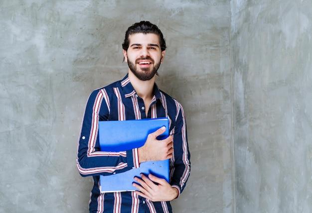 Homme tenant un dossier de rapport bleu et souriant.
