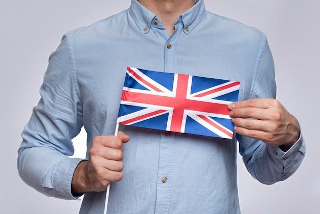 Homme tenant le drapeau du royaume-uni. étude de la langue anglaise. émigration vers le royaume-uni.